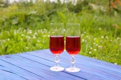 Twee glazen met eigengemaakte rode wijnstok op blauwe raad in openlucht in een platteland bij de zomer Stock Afbeelding