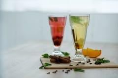 Twee glazen met gekleurde hete dranken waaruit de stoom komt dranken van de winter de hete seizoengebonden vitemin royalty-vrije stock foto