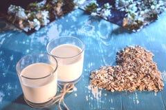 Twee glazen met havermelk in een rustieke stijl Vegetarisch ontbijt op een bloemachtergrond royalty-vrije stock foto