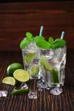 Twee glazen met niet-alkoholische die mojitococktail met lim wordt gediend Stock Foto