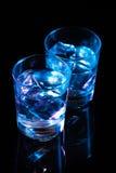 Twee glazen met wodka en ijsblokjes tegen de achtergrond van diep blauwe gloed op donkere spiegel Royalty-vrije Stock Foto