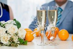 Twee glazen mousserende wijn en boeket van de bruid Stock Foto