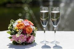 Twee glazen mousserende wijn en boeket van de bruid Royalty-vrije Stock Foto's