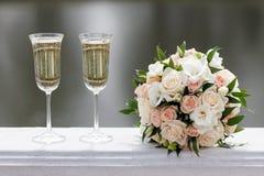Twee glazen mousserende wijn en boeket van de bruid Stock Foto's