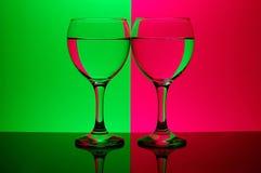 Twee glazen op neonachtergrond Stock Foto's