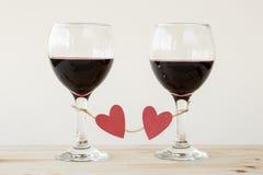 Twee glazen rode die wijn, met rode harten worden gebonden Stock Afbeeldingen