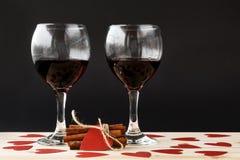 Twee glazen rode wijn en gebonden pijpjes kaneel met rode rond harten Stock Foto
