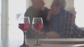 Twee glazen rode wijn en op achtergrond is silhouet van hoger paar Man de greepvrouw en kust haar neus stock footage