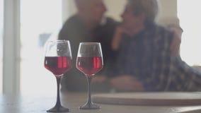 Twee glazen rode wijn en op achtergrond is silhouet van hoger paar Man de greepvrouw en kust haar neus Ploeter stock footage