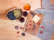 Twee glazen rode wijn, fig., kaas, bossen van druif en honing op houten lijst stock afbeelding