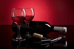 Twee glazen rode wijn, fles en crokcrew op rode en zwarte achtergrond Stock Foto's