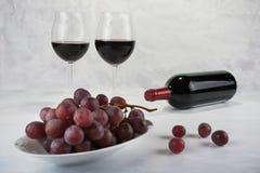 Twee glazen rode wijn met fles en druiven Royalty-vrije Stock Afbeeldingen