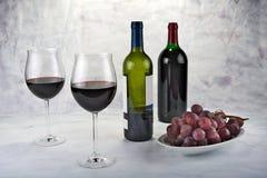 Twee glazen rode wijn met fles en druiven Stock Afbeelding