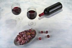 Twee glazen rode wijn met fles en druiven Stock Fotografie