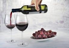 Twee glazen rode wijn met fles en druiven Stock Afbeeldingen