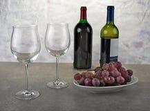 Twee glazen rode wijn met fles en druiven Stock Foto's
