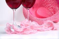 Twee glazen rode wijn op een witte achtergrond dichtbij roze damesslipjes Royalty-vrije Stock Foto