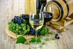 Twee glazen rode wijn, witte wijn, rode druiven, zwarte druiven, witte druiven, groene druiven, houten lijst, bladeren, vat, dran stock afbeeldingen
