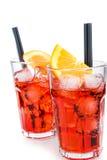 Twee glazen van aperolcocktail van het spritzaperitief met oranje die plakken en ijsblokjes op wit worden geïsoleerd Stock Afbeeldingen