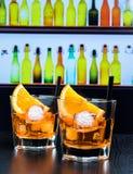 Twee glazen van aperolcocktail van het spritzaperitief met oranje plakken en ijsblokjes op barlijst, de achtergrond van de discoa Stock Foto's