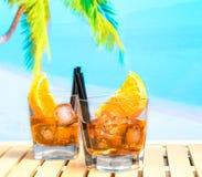 Twee glazen van aperolcocktail van het spritzaperitief met oranje plakken en ijsblokjes op de achtergrond van het onduidelijk bee Stock Foto