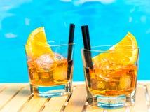 Twee glazen van aperolcocktail van het spritzaperitief met oranje plakken en ijsblokjes op zwembadachtergrond Stock Foto's