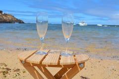 Twee Glazen van Champagne On The Beach With-Overzeese Bac Stock Afbeelding