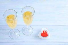 Twee glazen van fonkelende champagne en een rode hart-vormige kaars royalty-vrije stock afbeeldingen