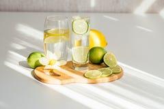 Twee glazen van water met citroen en kalk op een houten raad en een bloem van narcissen royalty-vrije stock foto