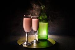 twee glazen van wijn en fles over gestemde mistige achtergrond Beeld van twee wijnglazen met champagne de overzichten en de silho Stock Foto's