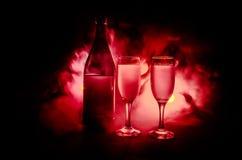 twee glazen van wijn en fles over gestemde mistige achtergrond Beeld van twee wijnglazen met champagne de overzichten en de silho Stock Fotografie