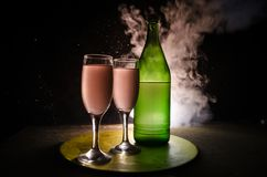 twee glazen van wijn en fles over gestemde mistige achtergrond Beeld van twee wijnglazen met champagne de overzichten en de silho Stock Foto