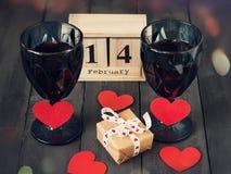 Twee glazen van wijn met een document hart en een kalender met een datum op 14 Februari, en een gift Op houten dark Royalty-vrije Stock Afbeeldingen