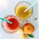 Twee glazen vers sap en fruit Twee kleurrijke fruitschokken De zomer en tropisch smoothies en fruit Gemengde koude royalty-vrije stock afbeelding