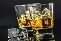 Twee glazen whisky dichtbij ijsblokjes op donkere achtergrond Stock Afbeelding