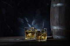 Twee glazen whisky met ijs en houten vat royalty-vrije stock afbeeldingen