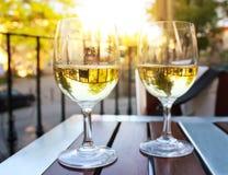 Twee glazen wijn bij zonsondergang met zongloed Stock Afbeelding