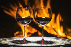 Twee glazen wijn op de achtergrond van brand Stock Afbeelding