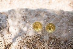 Twee glazen witte wijn bij kiezelsteenstrand stock fotografie