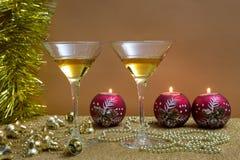 Twee glazen witte wijn en rode snuisterijen met kaarsen op gouden basis en bruine decoratie als achtergrond en gouden royalty-vrije stock afbeelding