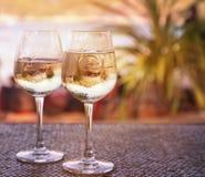 Twee glazen witte wijn met ijs op een lijst bij de strandkoffie Stock Foto's