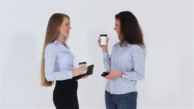 Twee glimlachende aantrekkelijke bureaumeisjes die en koffie spreken drinken stock footage