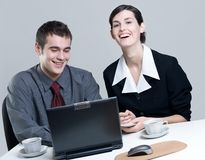 Twee glimlachende bedrijfsmensen op laptop Royalty-vrije Stock Foto's
