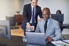 Twee glimlachende diverse zakenlieden die aan laptop samenwerken stock foto