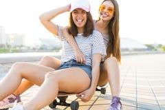 Twee glimlachende jonge meisjes die pret hebben terwijl het berijden op een skateboard bij het park stock foto