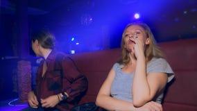 Twee glimlachende jonge vrouwen Aziatisch en Kaukasisch bij een lijst in een nachtclub stock footage