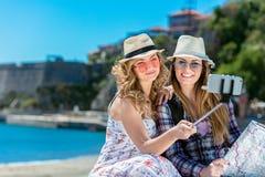Twee glimlachende jonge vrouwen die op stadsbank het maken zitten ziet terwijl samen het nemen van zelfportretten onder ogen stock foto's