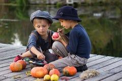 Twee glimlachende jongens schilderen kleine appelen Royalty-vrije Stock Foto