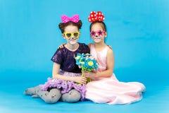 Twee glimlachende meisjes die in grappige zonnebril op blauwe achtergrond zitten Stock Foto's