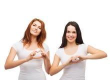 Twee glimlachende meisjes die hart met handen tonen Royalty-vrije Stock Foto's